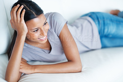 Buy stock photo Attractive mixed race woman smiling while lying on sofa