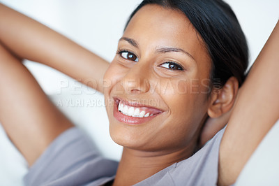 Buy stock photo Closeup portrait of beautiful mixed race woman smiling while resting on couch