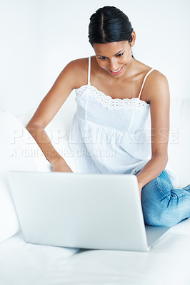 Buy stock photo Happy mixed race woman relaxing at home while using laptop
