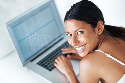 Buy stock photo Cheerful mixed race woman using laptop while lying on couch