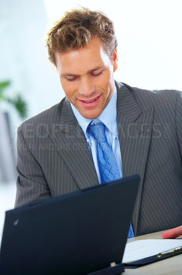 Buy stock photo Businessman in his office with a laptop doing paperwork