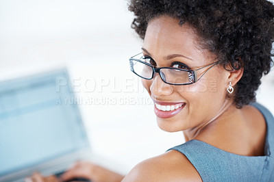 Buy stock photo Closeup of African American business woman in glasses smiling while working on laptop