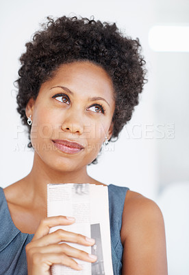 Buy stock photo Attractive business woman looking away holding newspaper in deep thought