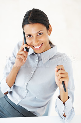 Buy stock photo High angle view of mixed race business woman smiling while talking on mobile phone