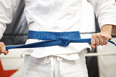 Buy stock photo Cropped shot of martial artist putting on his gi and tying his belt