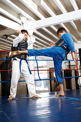 Buy stock photo Full length shot of two martial artists sparring in the ring
