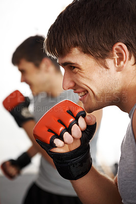 Buy stock photo Cropped shot of a young martial artist smiling during a fight