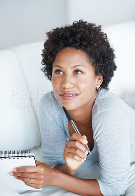 Buy stock photo Thoughtful African American woman writing in diary while lying on couch