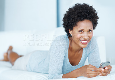 Buy stock photo Beautiful African American woman reading text message while lying in couch