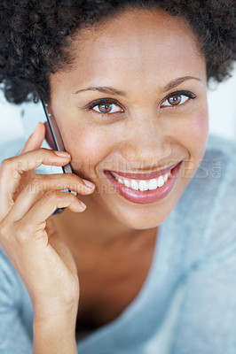 Buy stock photo Closeup portrait of beautiful young woman smiling while talking on mobile phone