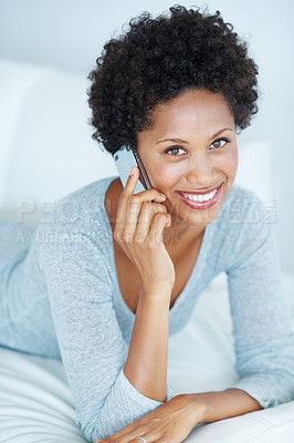 Buy stock photo Smiling young woman talking on mobile phone while lying on couch