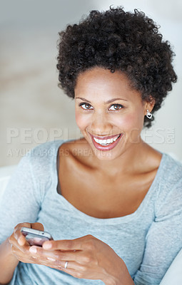 Buy stock photo Attractive young woman smiling while reading text message on couch