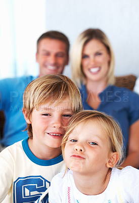 Buy stock photo Portrait of happy family smiling at home with focus on kids