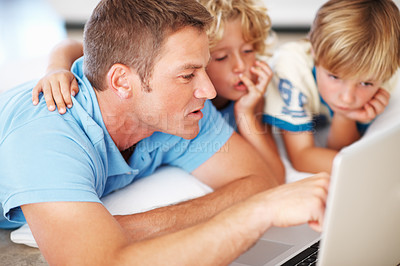 Buy stock photo Closeup of mid adult man using laptop with boys at home