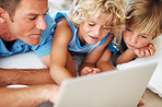 Cute kids using laptop with dad