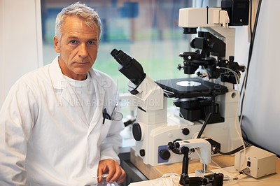Buy stock photo Portrait of confident male researcher working in laboratory with a microscope