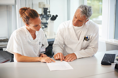 Buy stock photo Two lab assistants sitting together reading test results in laboratory