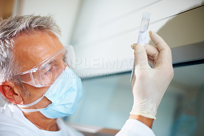 Buy stock photo Mature male lab analyst focusing on a test tube at laboratory
