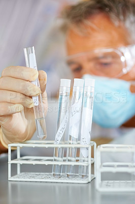 Buy stock photo Scientists hand examining test tubes in a laboratory