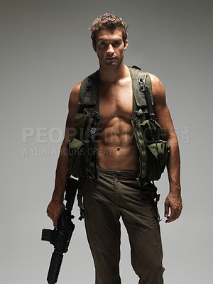 Buy stock photo Hunky young man with a bare chest and dressed in army clothing holding an M16 automatic rifle