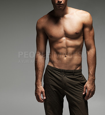 Buy stock photo Midsection view of a shirtless young man in a relaxed pose - cropped