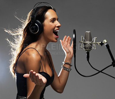 Buy stock photo Attractive young woman singing passionately into a cardioid microphone - isolated