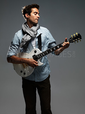 Buy stock photo Trendy young man intently concentrating while playing a white electric guitar