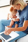 Woman using laptop with cute baby