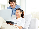 Smiling young couple using laptop on sofa at home