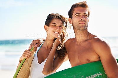 Buy stock photo Young couple looking on before heading out to surf - copyspace