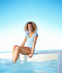 Happy young woman sitting by swimming pool and smiling