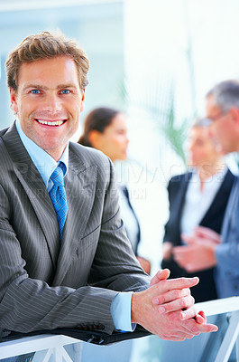 Buy stock photo Confident businessman smiling with his colleagues in the background