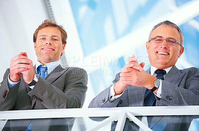 Buy stock photo Two Business executives smiling. Picture taken from below and with a blue sky in the background.