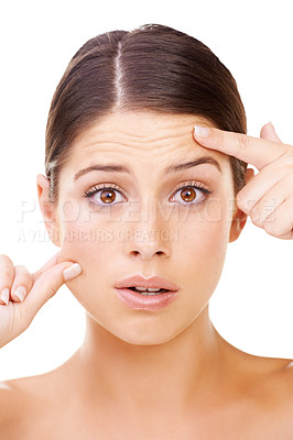 Buy stock photo Studio portrait of a beautiful young woman looking worried about her complexion isolated on white