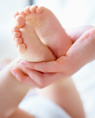 Buy stock photo Cropped close up shot of a mother holding her baby's feet