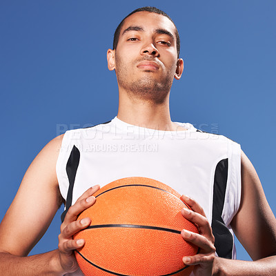 Buy stock photo A young sportsman clutching a basketball
