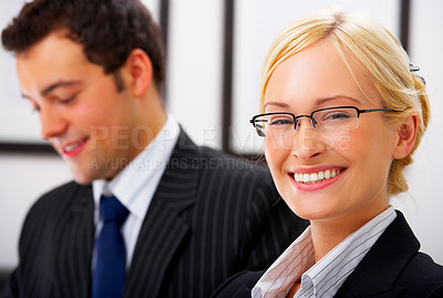 Buy stock photo Two business people in an office - Portrait of an adorable business executive in an office with a male colleague in the background.