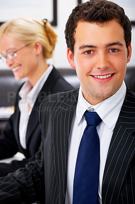 Buy stock photo Portrait of a ambitious business man in an office. With a beautiful female colleague in the background.
