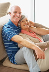 Portrait of a happy senior couple sitting together in house