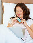 Pretty woman relaxing on bed , using credit card to shop online