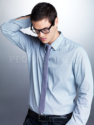 Buy stock photo Portrait of an attractive young businessman thinking against grey background