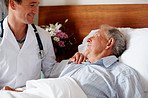 Young doctor visiting a senior patient at his bed