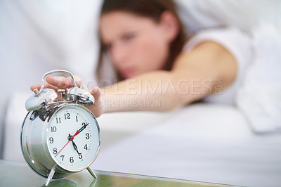 Buy stock photo A young woman pressing the stop button on her alarm clock