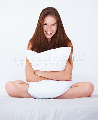 Buy stock photo A beautiful young woman holding a pillow while sitting on her bed