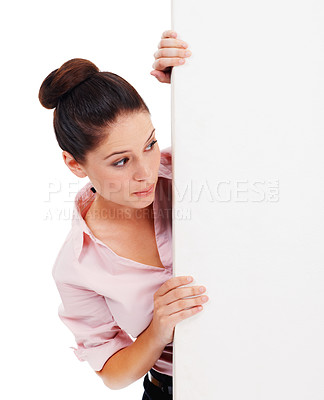 Buy stock photo Shot of a young woman looking from behind at a large blank placard isolated on white