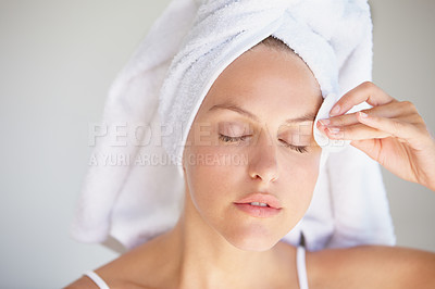 Buy stock photo Closeup shot of an attractive young woman with her hair wrapped in a towel removing makeup