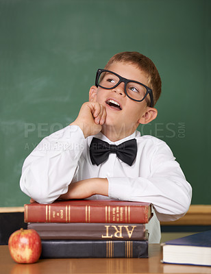 Buy stock photo A schoolboy sitting behind a pile of books looking up thoughtfully