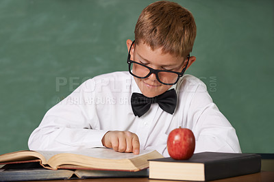 Buy stock photo A young boy wearing glasses and a bow-tie concentrating on his reading with a red apple on the table in front of him