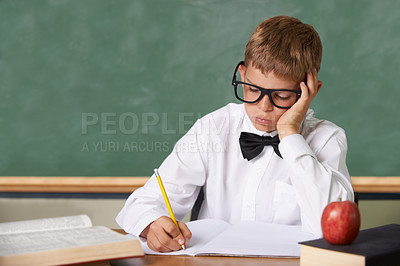 Buy stock photo A young boy with glasses and a bow-tie sitting in class writing despondently in a book