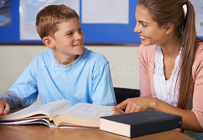 Buy stock photo A beautiful teacher explaining something to her young pupil